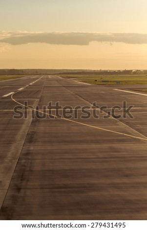 Empty runway at the airport, the prospect of the distance to the horizon in anticipation of landing the plane. Sunset. Concept travel. - stock photo