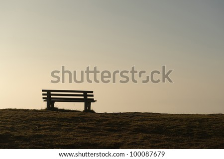 Empty rustic wooden bench on the skyline silhouetted against the delicate glow of an early morning sunrise or evening sunset - stock photo