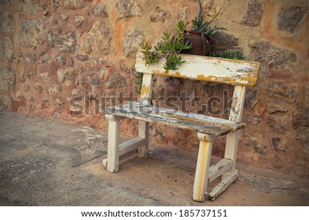 Empty Rustic wooden outdoor cottage bench painted white against wall - stock photo