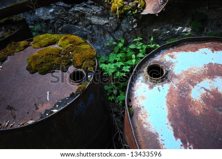 Empty rusting toxic chemical barrels - stock photo