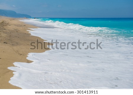 empty sandy beach. blue waves, sand beach and blue sky. Greece, the island of Lefkada, Yialos Beach, Gialos