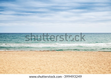 Empty sandy beach. Mediterranean sea coast under cloudy sky, natural background photo - stock photo