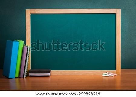 Empty school blackboard with books and sponge - stock photo