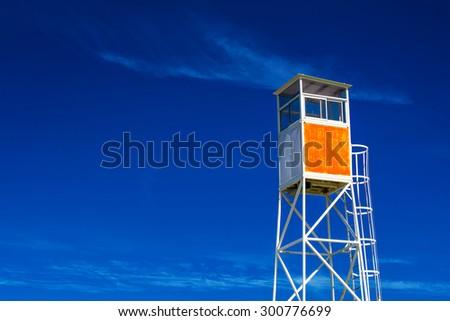 Empty Seaside Coastal Lifeguard Watchtower Against Blue Sky - stock photo