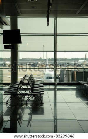 Empty seats in a waiting lounge in an airport terminal, overlooking the airfield and airplanes outside - stock photo