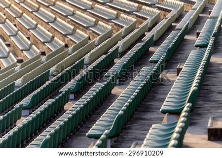 Empty seats in outdoor stadium during late afternoon. - stock photo