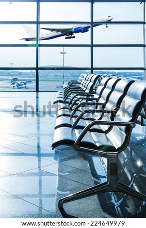 Empty seats in the departure lounge at the airport and airplane taking off - stock photo