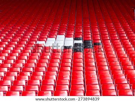 Empty seats red around white and black at stadium. - stock photo