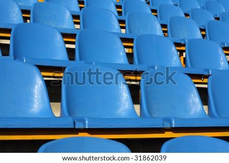 Empty section of blue seats on stadium - stock photo