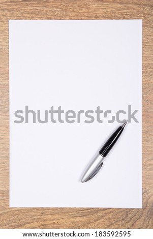 empty sheet of paper and pen on wooden table