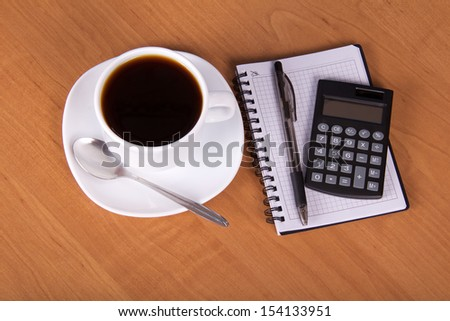 Empty sheets for notes, the handle the calculator and a cup of coffee on a table