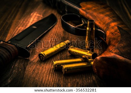 Empty shells with rifle and combat knife lying on a wooden table. Close up view, focus on the shells, image vignetting and the orange-blue toning - stock photo