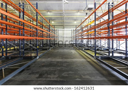 Empty shelves and racks in distribution warehouse - stock photo