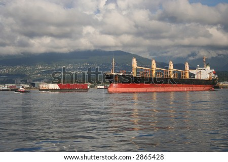 Empty ship and tug pulling barge with container