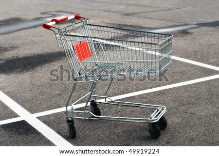 Empty shopping cart at the supermarket parking lot - stock photo
