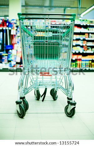 Empty shopping cart in big store with products and few people in background. Shop concept - stock photo