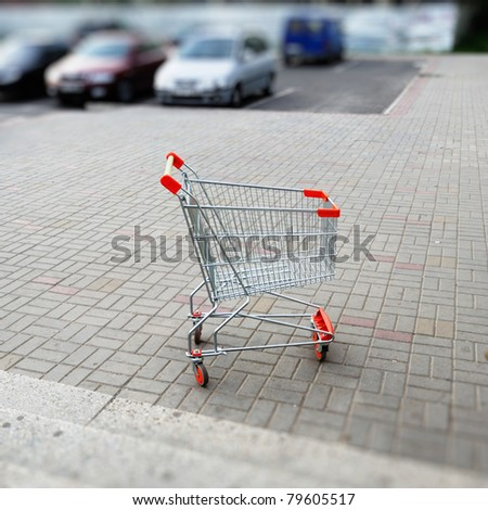 Empty shopping cart in parking lot. Useful file for your article about globalization,  etc - stock photo