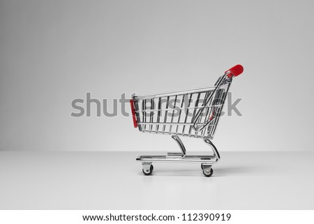 Empty shopping cart on gray background. Side view
