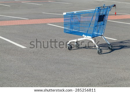 Empty shopping cart stands on a parking near supermarket - stock photo