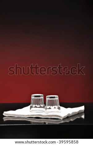 empty shot glass on a bar with a red background