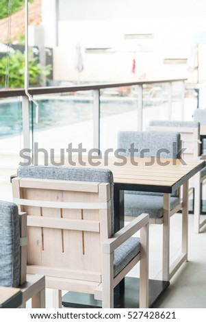 Empty sidewalk cafe with chairs and pillow