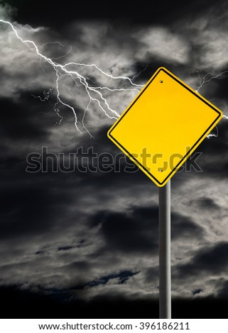 Empty sign against a dark, cloudy and thunderous sky. Conceptually warning of danger ahead. Blank sign for copy space and message. Vertical orientation