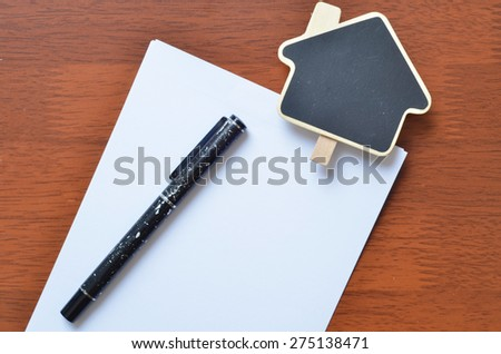 Empty sign clip and pen over the white blank paper - stock photo