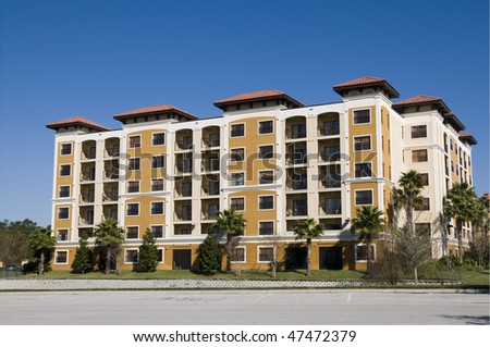 Empty Six story Florida Condominiums surrounded by palm trees - stock photo
