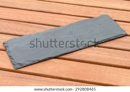 Empty Slate - Black serving platter on a wooden table outdoors.  - stock photo