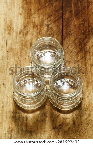 Empty small glass jar on a wooden table, selective focus - stock photo