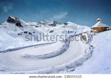 Empty snow covered mountain road in winter landscape - stock photo