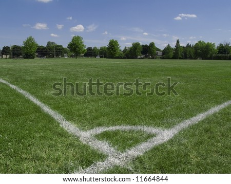 Empty soccer field under summer sun - stock photo