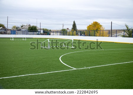Empty soccer field with green grass and overturned the gateway to the village - stock photo