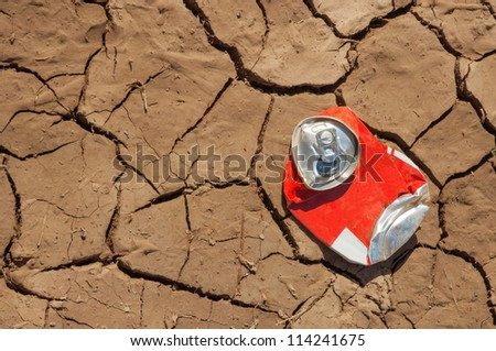 empty soda can on very dry soil - stock photo