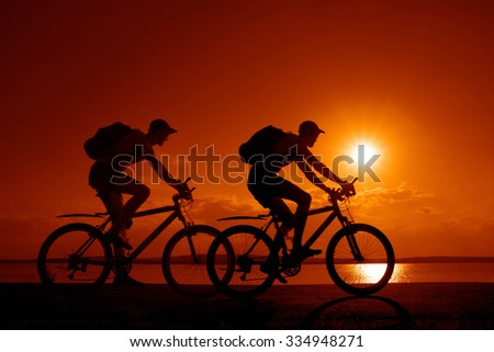 Empty Space Sporty friends on bicycle on sunset Silhouette couple cyclist go along shoreline coast Sport in Nature background Group of people two mountain biker in sunrise with reflection sun in water