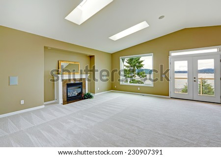 Empty spacious living room with walkout deck and fireplace. Room with high vaulted ceiling and skylights. - stock photo