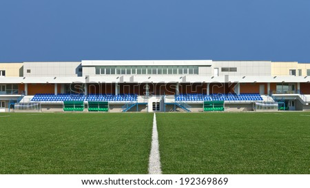 Empty sports field with the white line markings and grandstand stadium - stock photo