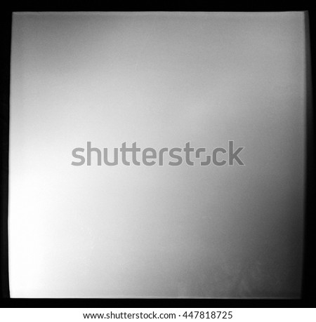 Empty square black and white film frame with heavy grain and light leak - stock photo