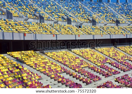 Empty Stadium Tribune - Rows of folded, green, plastic seats in very big, empty stadium - stock photo