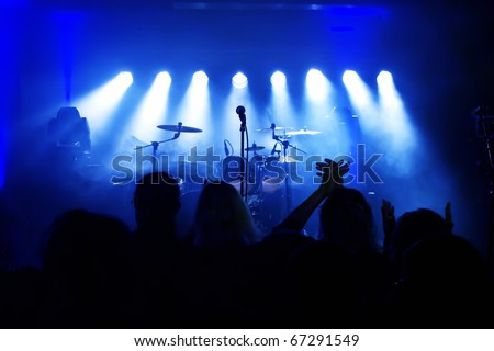 Empty Stage at concert, concert crowd in front of bright blue stage lights - stock photo