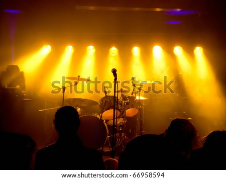 Empty Stage at concert, concert crowd in front of bright yellow stage lights - stock photo