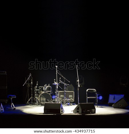 Empty stage at concert, drum kit, microphones and audio speakers