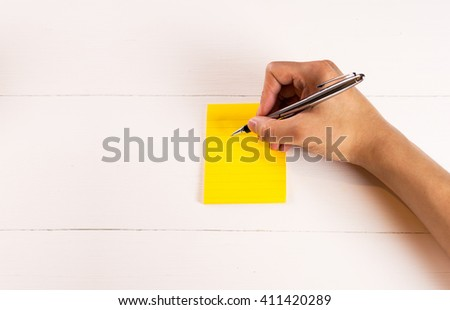Empty sticky post with man hand writing on white wood - stock photo