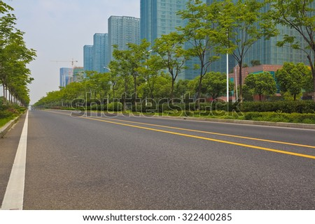 Empty straight line road surface with modern city buildings background - stock photo