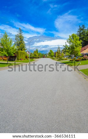 Empty street at the nice and comfortable great neighborhood, community. Some homes on the empty street in the suburbs of Vancouver, Canada. Vertical. - stock photo