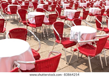 empty street cafe with red chairs on a square