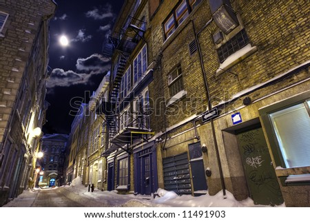 Empty street in a winter night highlighted by moon - stock photo