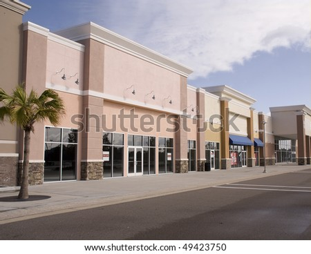 empty strip mall with pastel stucco and stone accents - stock photo