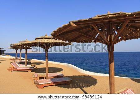 empty sunbathe and beach umbrella in Sharm El Sheik - stock photo