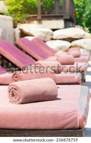 empty sunbed with wrapped towels on a beautiful beach on sunny day - stock photo